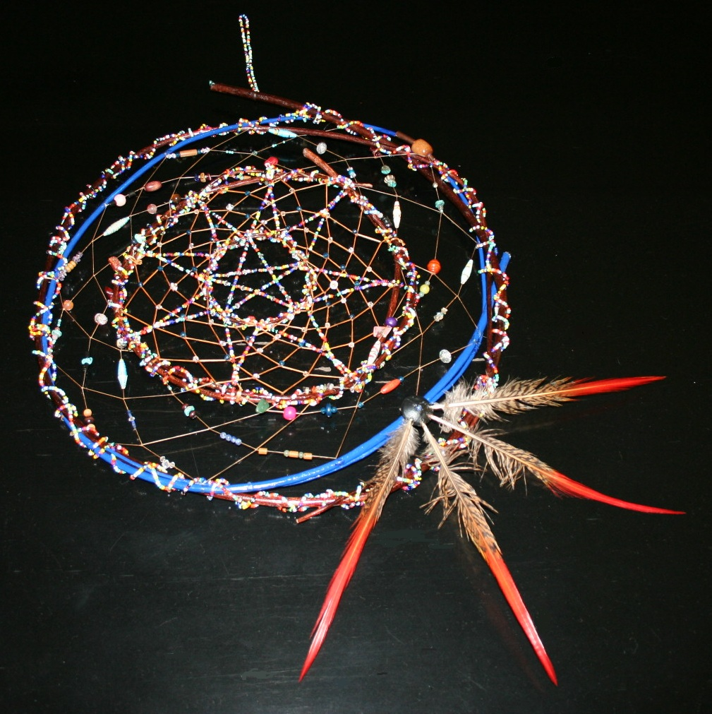 summer solstice dreamcatcher by john pete with four hoops, beaded star and bead embellishments, with colorful feathers